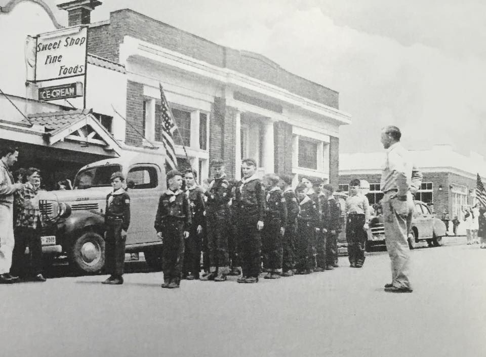 Historic Image - 4th of July Parade, Boy Scouts in front of State Bank and Sweet Shop